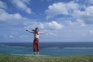 ジャンプをする女の子と海と青空の写真素材 [FYI04058372]