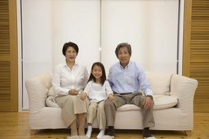 ソファに座る女の子と祖父母の写真素材 [FYI04058402]
