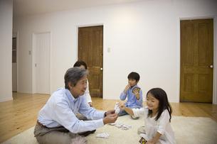 リビングでトランプをする子供と祖父母の写真素材 [FYI04058408]