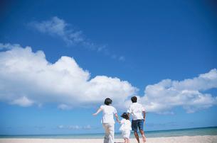 ビーチを走る家族の後ろ姿と入道雲の写真素材 [FYI04058416]