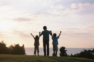 丘の上に立つ家族のシルエットの写真素材 [FYI04058432]
