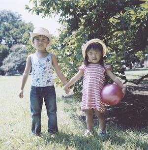 木陰で手を繋ぐ男の子とボールを持った女の子 日本人の写真素材 [FYI04058438]