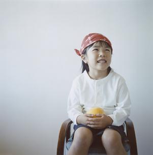 グレープフルーツを持つバンダナを巻いた日本人の女の子の写真素材 [FYI04058448]