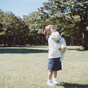 公園で犬を抱えた日本人の女の子の写真素材 [FYI04058454]