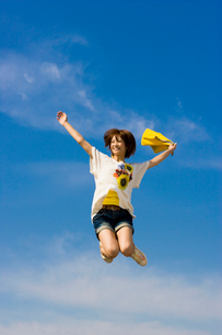 青空と元気にジャンプする女子大学生の写真素材 [FYI04058484]