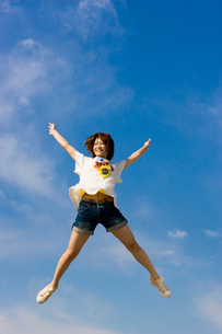 青空と元気にジャンプする女子大学生の写真素材 [FYI04058485]
