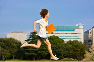 勉強道具を持って走る若い女子大学生の写真素材 [FYI04058491]