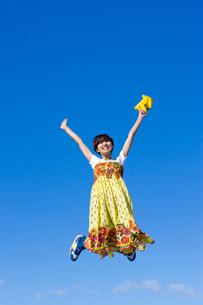 青空とジャンプする若い女子大学生の写真素材 [FYI04058499]