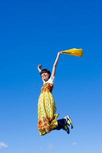 青空とジャンプする若い女子大学生の写真素材 [FYI04058500]