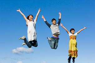青空とジャンプする3人の大学生の写真素材 [FYI04058503]