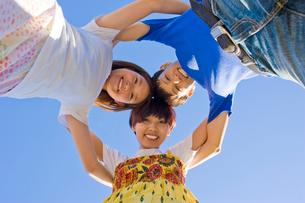 円陣を組む笑顔の男女3人の大学生と青空の写真素材 [FYI04058519]