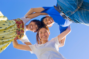 円陣を組む笑顔の男女3人の大学生と青空の写真素材 [FYI04058520]