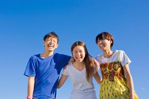 肩を組んで笑う若い男女3人の大学生と青空の写真素材 [FYI04058522]