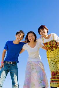 肩を組んで笑う若い男女3人の大学生と青空の写真素材 [FYI04058523]