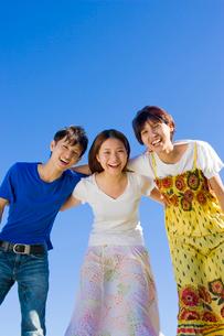肩を組んで笑う若い男女3人の大学生と青空の写真素材 [FYI04058527]