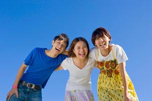 肩を組んで笑う若い男女3人の大学生と青空の写真素材 [FYI04058529]