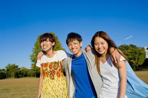 青空と笑顔で歩く若い男女3人の大学生の写真素材 [FYI04058537]