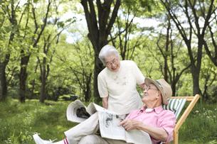 庭で新聞を読む日本人シニア夫婦の写真素材 [FYI04058589]