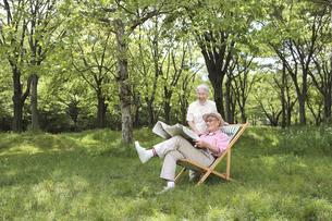 庭で新聞を読む日本人シニア夫婦の写真素材 [FYI04058592]