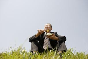 土手に座って弁当を食べるサラリーマンの写真素材 [FYI04058595]
