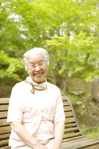 公園のベンチに座るシニア女性の写真素材 [FYI04058612]