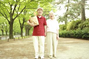 買い物袋を持って並木道を歩くシニア夫婦の写真素材 [FYI04058618]