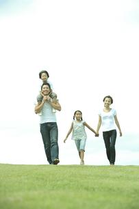 公園の芝生を歩く4人家族の写真素材 [FYI04058640]