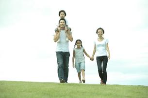 公園の芝生を歩く4人家族の写真素材 [FYI04058643]
