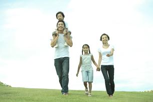 公園の芝生を歩く4人家族の写真素材 [FYI04058646]