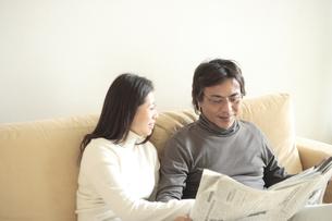 ソファーに座り新聞を読む夫婦の写真素材 [FYI04058653]