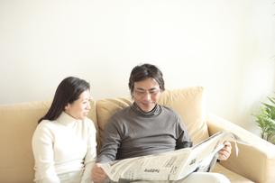 ソファーに座り新聞を読む夫婦の写真素材 [FYI04058654]