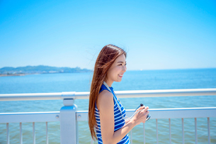 海の上の橋で写真を撮るリゾートへ旅する女性の写真素材 [FYI04058841]
