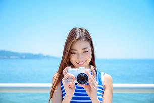 海の上の橋で写真を撮るリゾートへ旅する女性の写真素材 [FYI04059010]