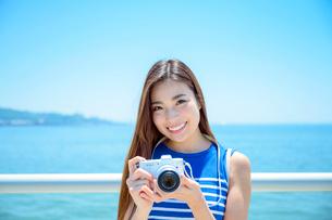 海の上の橋で写真を撮るリゾートへ旅する女性の写真素材 [FYI04059053]