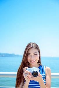 海の上の橋で写真を撮るリゾートへ旅する女性の写真素材 [FYI04059068]