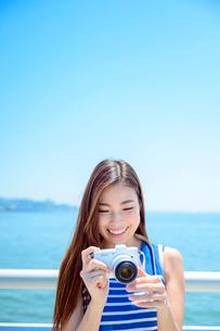 海の上の橋で写真を撮るリゾートへ旅する女性の写真素材 [FYI04059076]