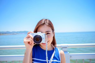 海の上の橋で写真を撮るリゾートへ旅する女性の写真素材 [FYI04059155]