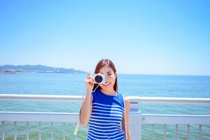 海の上の橋で写真を撮るリゾートへ旅する女性の写真素材 [FYI04059163]