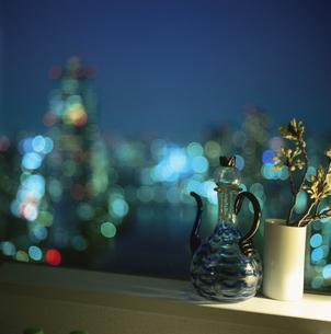 窓辺に置いた水差しと街の灯りの写真素材 [FYI04059321]
