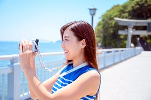 海の上の橋で写真を撮るリゾートへ旅する女性の写真素材 [FYI04059357]