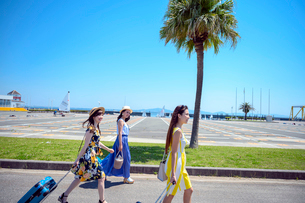 キャリーバッグを引き歩く海のリゾートへ旅する女性3人の写真素材 [FYI04059699]