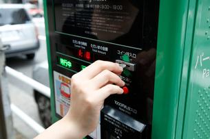 路上駐車代を支払う女性の写真素材 [FYI04059831]