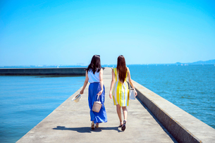 港の防波堤を歩く海のリゾートへ旅する女性2人の写真素材 [FYI04060034]
