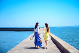 港の防波堤を歩く海のリゾートへ旅する女性2人の写真素材 [FYI04060101]