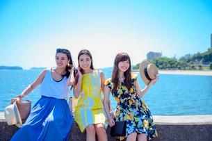港の防波堤に座る海のリゾートへ旅する女性3人の写真素材 [FYI04060182]