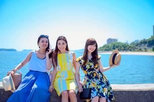 港の防波堤に座る海のリゾートへ旅する女性3人の写真素材 [FYI04060194]