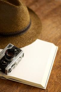 白紙の本とカメラと帽子の写真素材 [FYI04060596]