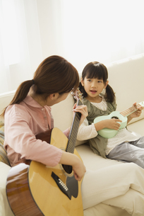 ソファに座ってギターを弾く母娘の写真素材 [FYI04061129]