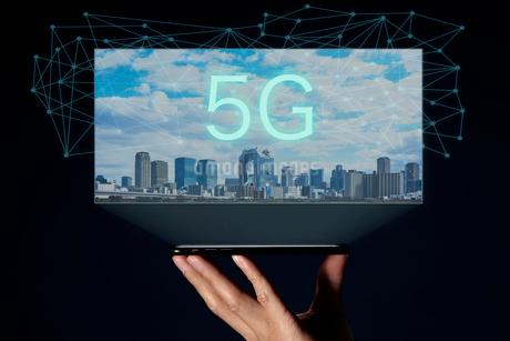 スマートフフォンから浮かび上がるビル群と青い線と5Gの文字の写真素材 [FYI04062172]