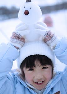 雪だるまを頭の上に乗せる女の子の写真素材 [FYI04063849]